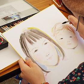 学生がイベントで似顔絵制作